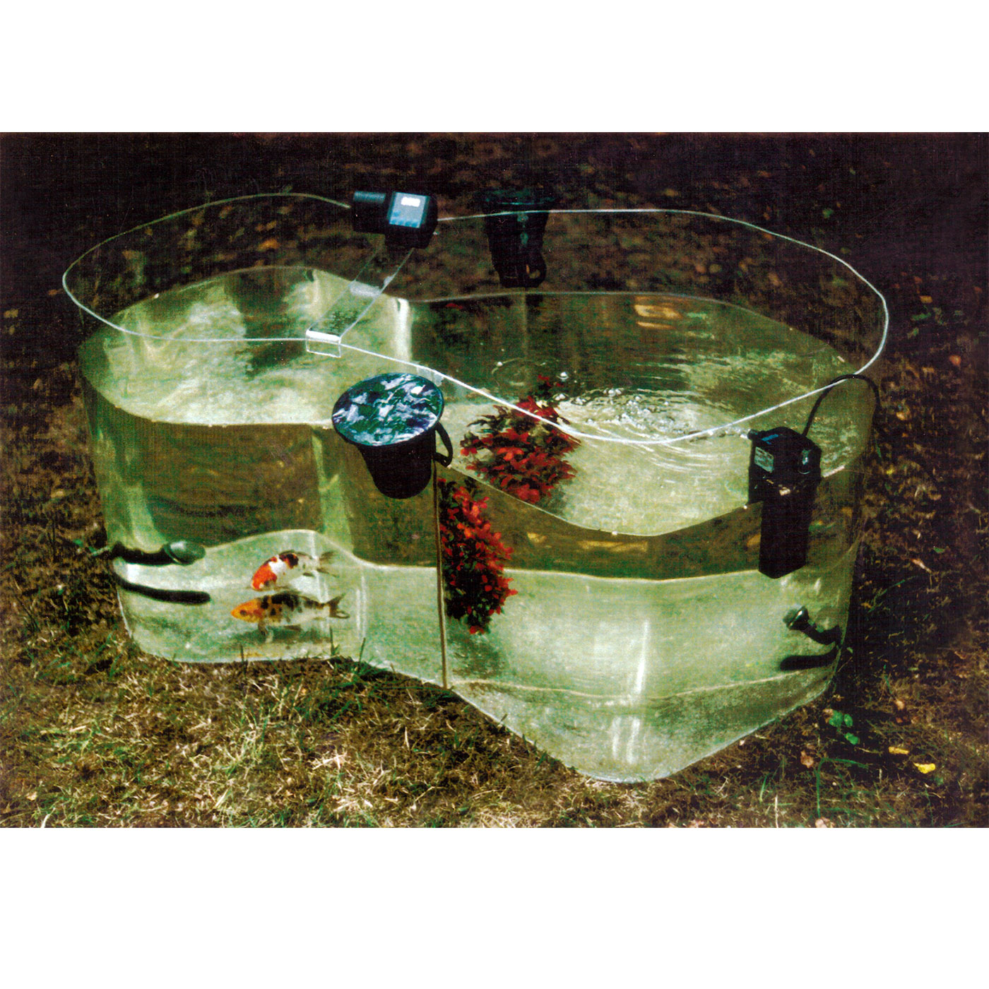 RUNNING GAG, © 1997, acrylic perspex, 2 microfones, 2 speakers, plastic flowers, 2 fishes (kois), water, 120 x 60 x 50 cm